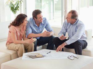 Imagen de pareja hablando con un asesor inmobiliario